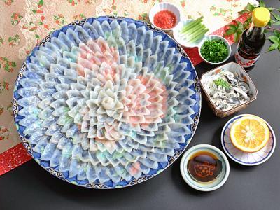 Sashimi di Fugu (Pesce Palla) servito a Crisantemo su piatto da 36cm e ciotola di Striscioline di pelle Scottate, accompagnato da Acero tritato, Aglietto Fresco, Erba Cipollina, Arancio e Salsa di Soia - 296euro.
